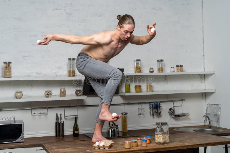 Креативное фото мускулистого человека на кухне балансирующего яйца стоковое фото