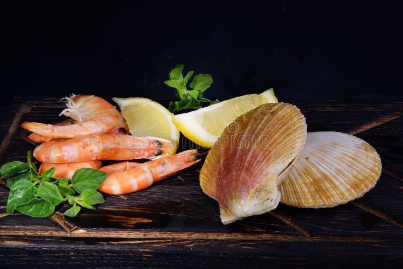 Креветки и scallops в раковинах лежат рядом с другими ингредиентами перед варить стоковое изображение