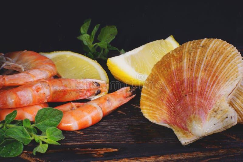 Креветки и scallops в раковинах лежат с лимоном и травами на темной доске перед варить стоковое фото rf