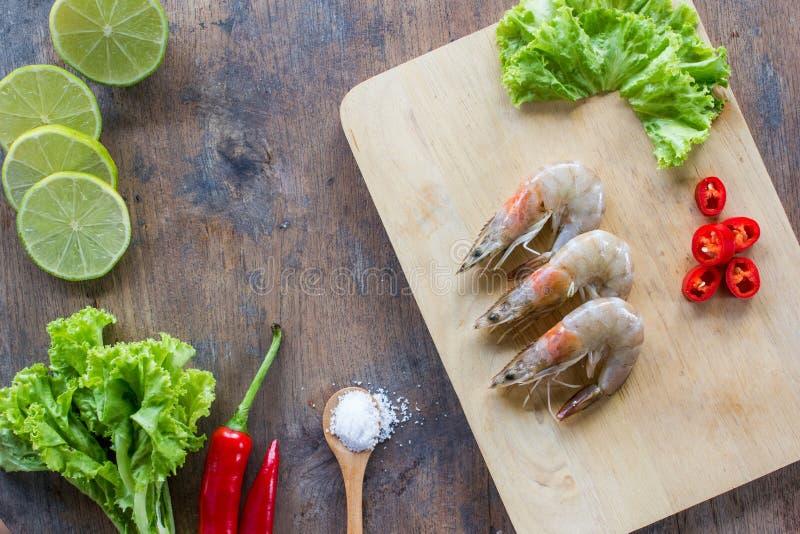 Креветки на деревянной плите с салатом, известкой, красными перцами и солью на предпосылке деревянного стола скопируйте космос Ин стоковое изображение