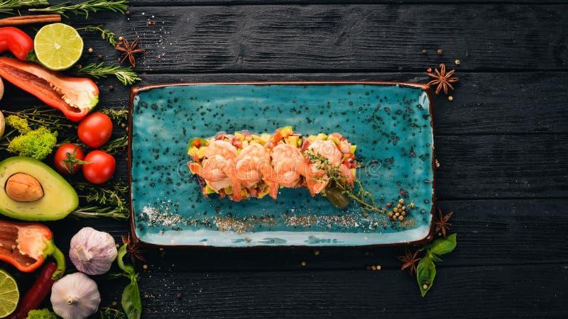 Креветки тигра на подушке авокадоа и свежих овощах стоковая фотография rf