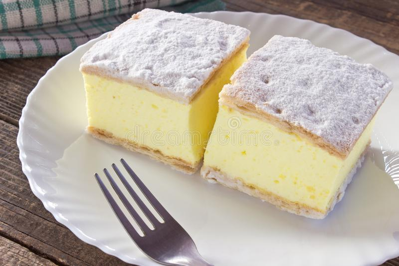 Кремовый пирог с слоями печенья слойки в плите на деревянном столе стоковое изображение rf