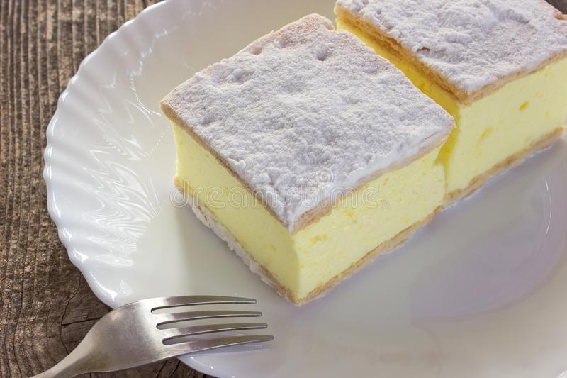 Кремовый пирог с слоями печенья слойки в плите на деревянном столе стоковое изображение