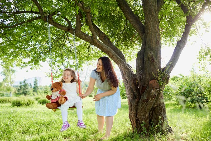 Крены мамы на ` s ребенка отбрасывают в парке в лете стоковые фото
