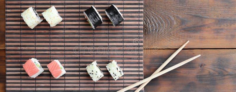 Крены суш и деревянные палочки лежат на циновке бамбуковой соломы serwing азиатские овощи зажаренного риса еды традиционные Взгля стоковые фото