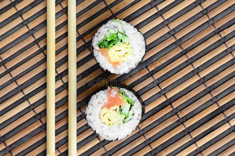 Крены суш и деревянные палочки лежат на циновке бамбуковой соломы serwing азиатские овощи зажаренного риса еды традиционные Взгля стоковое изображение rf
