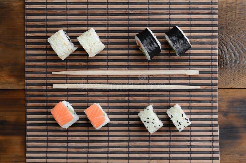 Крены суш и деревянные палочки лежат на циновке бамбуковой соломы serwing азиатские овощи зажаренного риса еды традиционные Взгля стоковая фотография rf