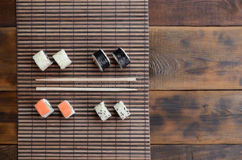 Крены суш и деревянные палочки лежат на циновке бамбуковой соломы serwing азиатские овощи зажаренного риса еды традиционные Взгля стоковое фото
