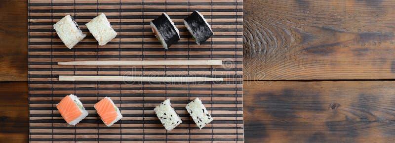 Крены суш и деревянные палочки лежат на циновке бамбуковой соломы serwing азиатские овощи зажаренного риса еды традиционные Взгля стоковые фотографии rf