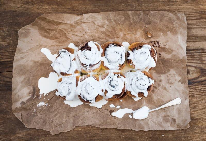 Крены циннамона с замороженностью плавленого сыра на части маслообразной бумаги ремесла над деревенской деревянной предпосылкой стоковые изображения