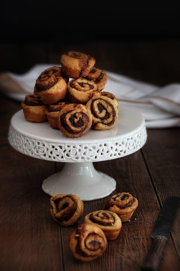 Крены pinwheel циннамона на стойке торта стоковые фото