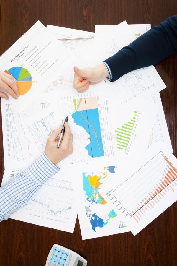 Кренящ, таксирующ и все связанные вещи с миром финансов - 2 бизнесмена делая согласование над таблицей с некоторым финансовым d стоковое фото