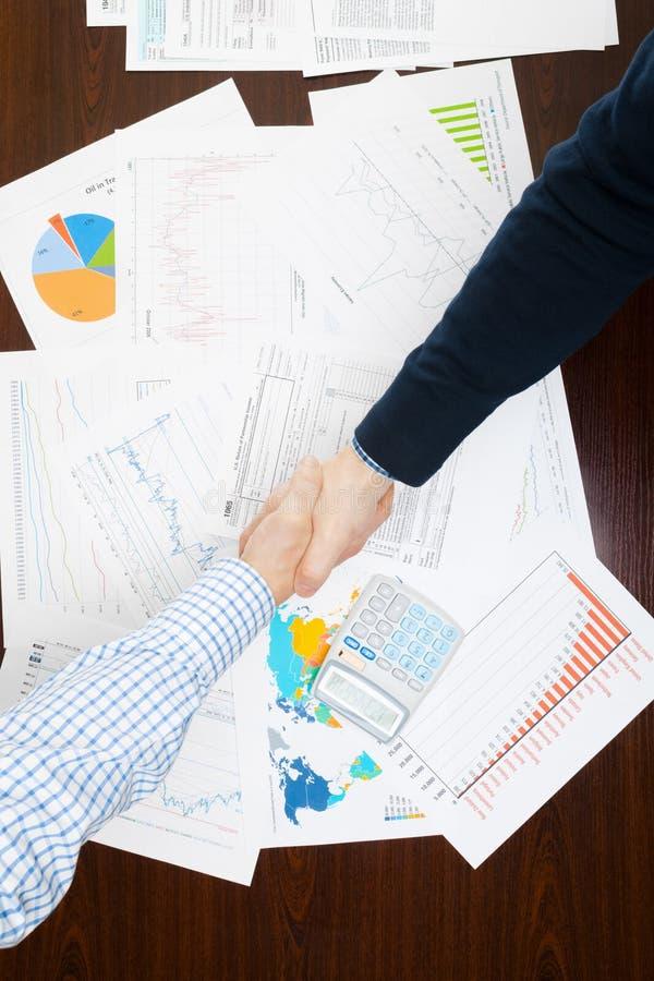 Кренящ, таксирующ и все связанные вещи с миром финансов - 2 бизнесмена тряся руки над таблицей с некоторыми финансовыми данными стоковая фотография