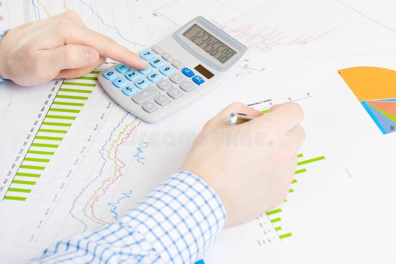 Кренящ, таксирующ и все связанные вещи с миром финансов - бизнесменом занятым делающ некоторые вычисления на столе стоковые фото