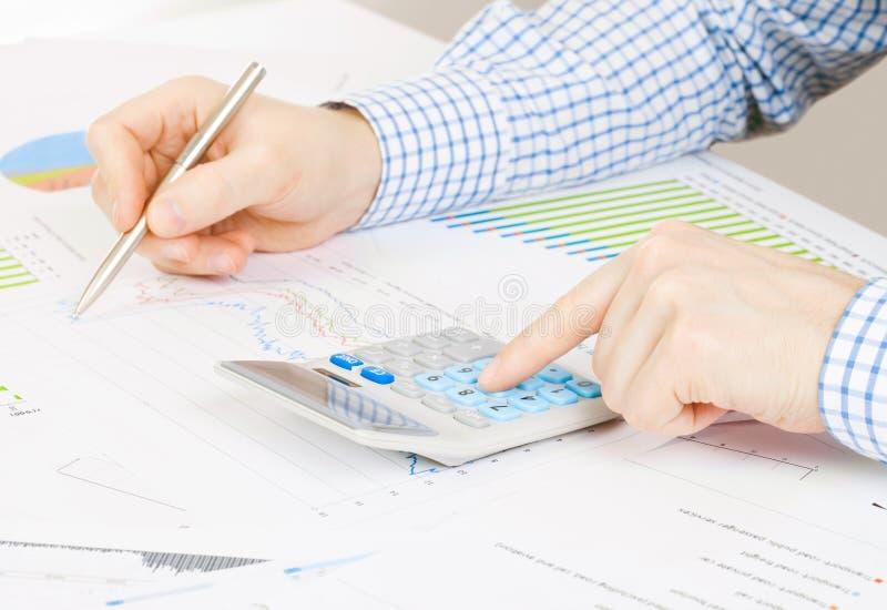 Кренящ, таксирующ и все связанные вещи с миром финансов - бизнесменом занятым с некоторыми вычислениями на столе стоковое фото