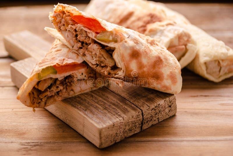 Крен говядины Shawarma гироскопов Doner Kebab в сэндвиче обруча хлеба pitta на деревянной предпосылке стоковые фото