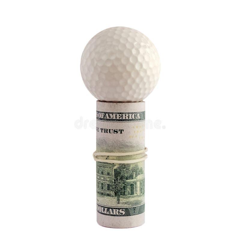 Крен долларовых банкнот американца 100 связанных с белой круглой резинкой с шаром для игры в гольф на верхней части изолят Концеп стоковое изображение