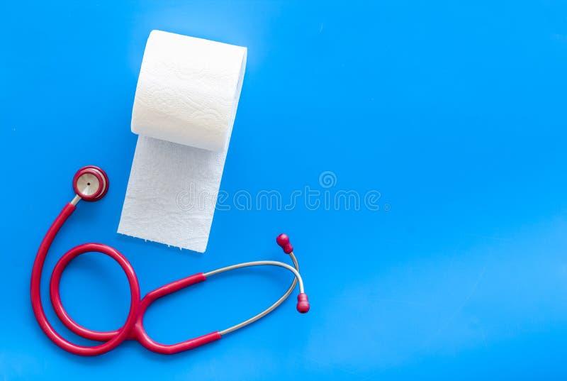Крен и стетоскоп туалетной бумаги для концепции заболеваниями проктологии на голубом модель-макете взгляда сверху предпосылки стоковое фото rf