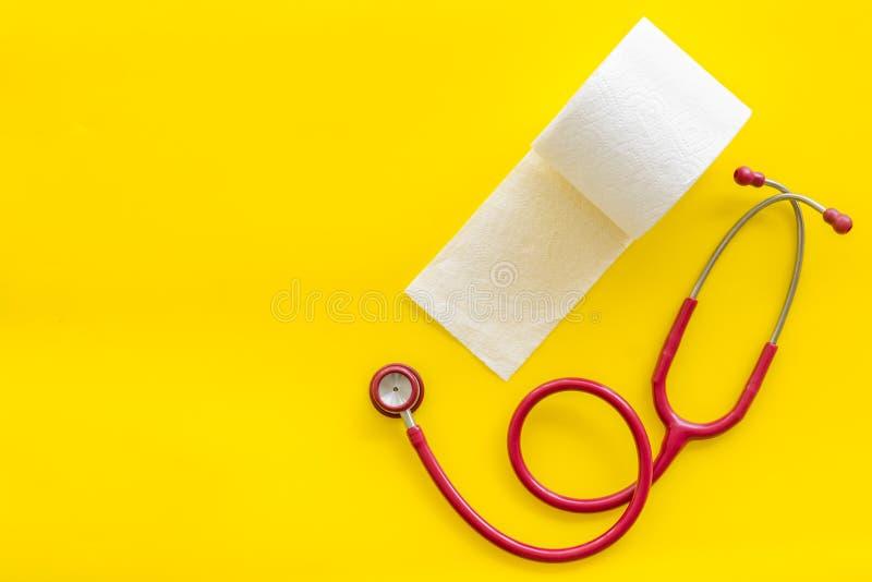 Крен и стетоскоп туалетной бумаги для концепции заболеваниями проктологии на желтой насмешке взгляда сверху предпосылки вверх стоковая фотография rf