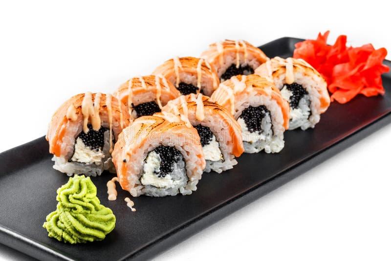 Крен суш - суши Maki сделанные из зажаренных семг, черной икры и плавленого сыра на черной плите изолированной над белой предпосы стоковые изображения