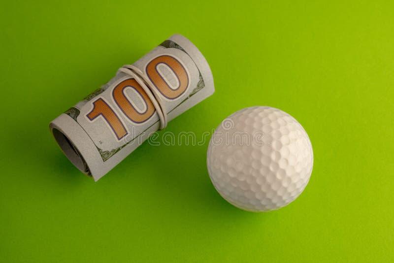 Крен 100 счетов доллара США связанных с белой круглой резинкой лежит рядом с шаром для игры в гольф против зеленой предпосылки _ стоковые фото