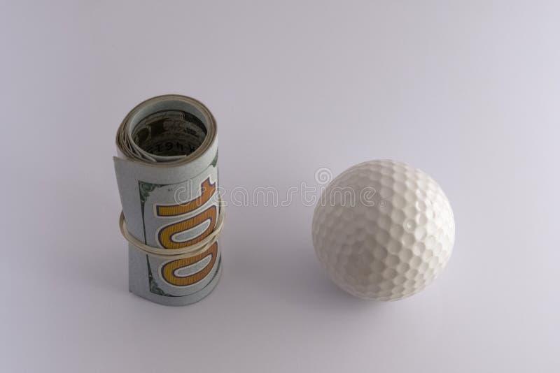 Крен 100 счетов доллара США связанных с круглой резинкой рядом с шаром для игры в гольф на белой предпосылке Концепция спорт стоковое фото rf