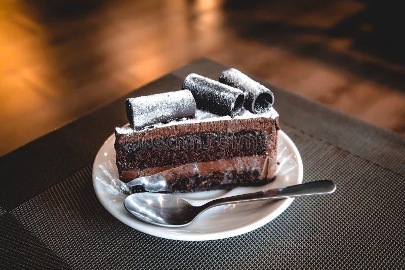 Крен шоколада wite торта пирожного на верхней части положенной на белую керамическую плиту имеет чайную ложку стоковое изображение rf