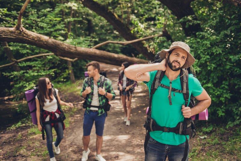 Крепко, трудная, утомляя и выматываясь экспедиция 4 друзей в одичалом лесе в следе Гай бороться боли шеи, massa стоковые изображения