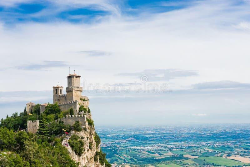 Крепость Guaita на Monte Titano с городом Сан-Марино в backgro стоковые изображения