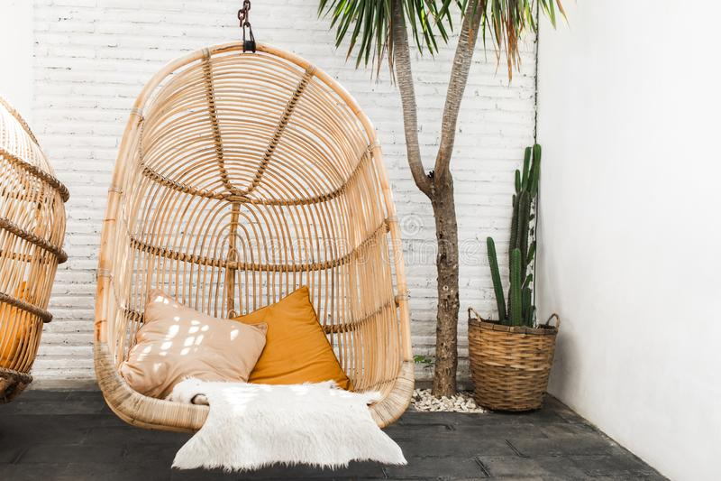 Кресло для отдыха плетеного ротанга вися в кафе просторной квартиры стоковая фотография