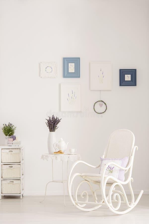 Кресло-качалка рядом с таблицей с лавандой цветет в белом интерьере живущей комнаты с плакатами Реальное фото стоковые фото