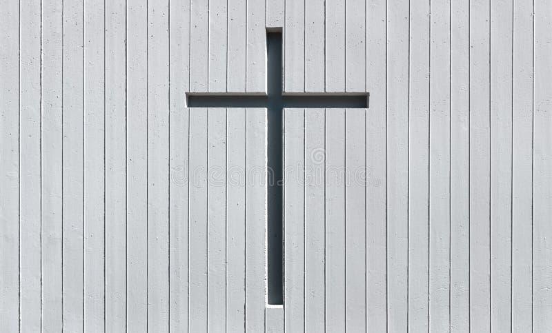 Крест в белой стене сделанной из, который подвергли действию бетона стоковое изображение