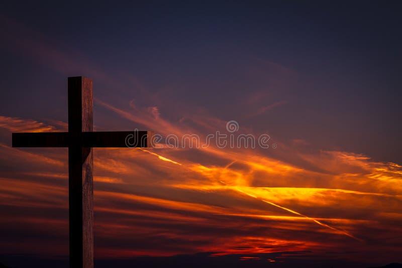 Крест Иисуса Христоса деревянный на предпосылке с драматическим, красочным заходом солнца, и апельсином, фиолетовым небом
