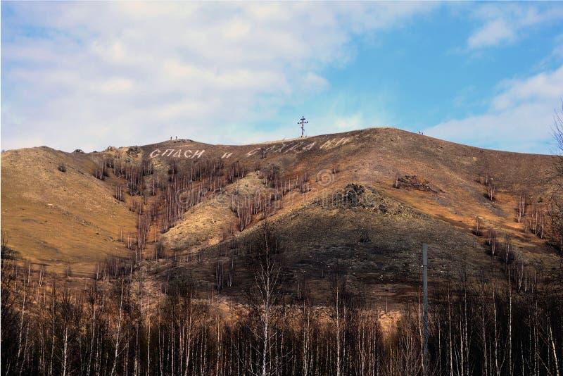 Крест и надпись на горе ' благословите и save' Karabash, Россия стоковые фотографии rf
