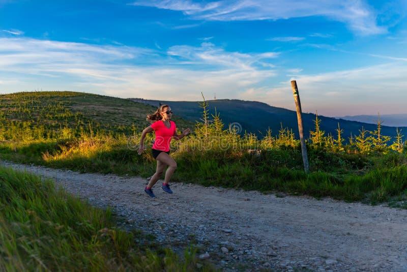 Крест молодой женщины бежать в горах на лете стоковые изображения
