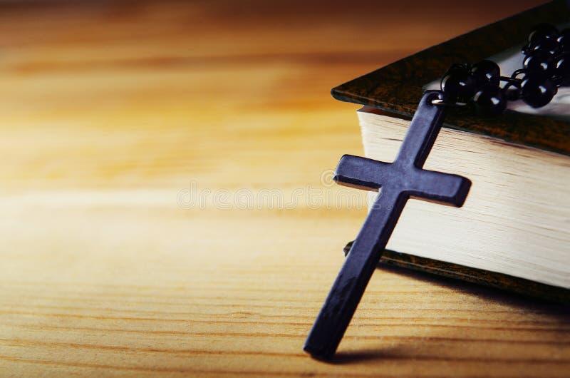Крест на потоке с черными шариками с библией на деревянном столе Религиозный символ, молитва скопируйте космос стоковые изображения rf