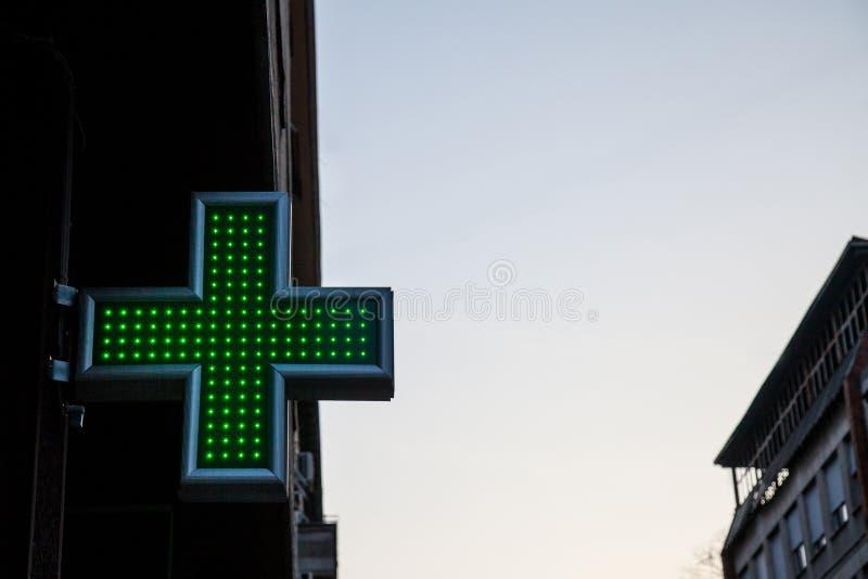 Крест фармации зеленый осветил с неоном и светами СИД в заходе солнца Этот крест всеобщий символ для фармации в Европе стоковые фото