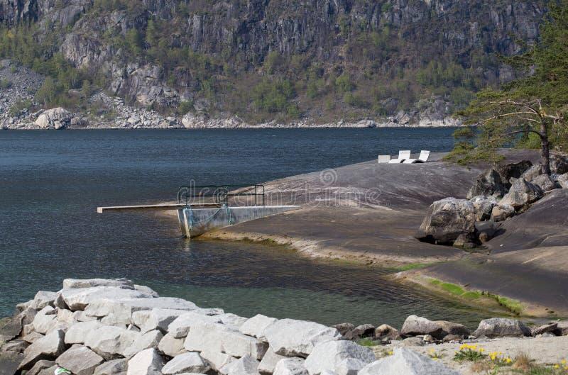 Кресла для отдыха доски и камня подныривания на естественной купая платформе на солнечный день, Eidfjord, Hordaland стоковое фото