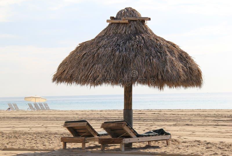 Кресла для отдыха хаты и древесины Tiki на пляже стоковое изображение