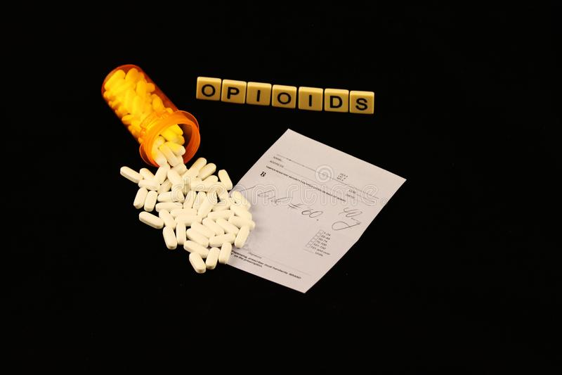 Кризис Opioid сказал по буквам вне на черной предпосылке с разлитыми пилюльками рецепта на пусковой площадке рецепта стоковые фото