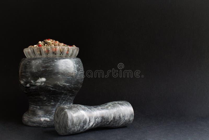 Кристаллическая плита со смешиванием сухих покрашенных стоек перцев на миномете для меля специй рядом с молотком стоковое фото