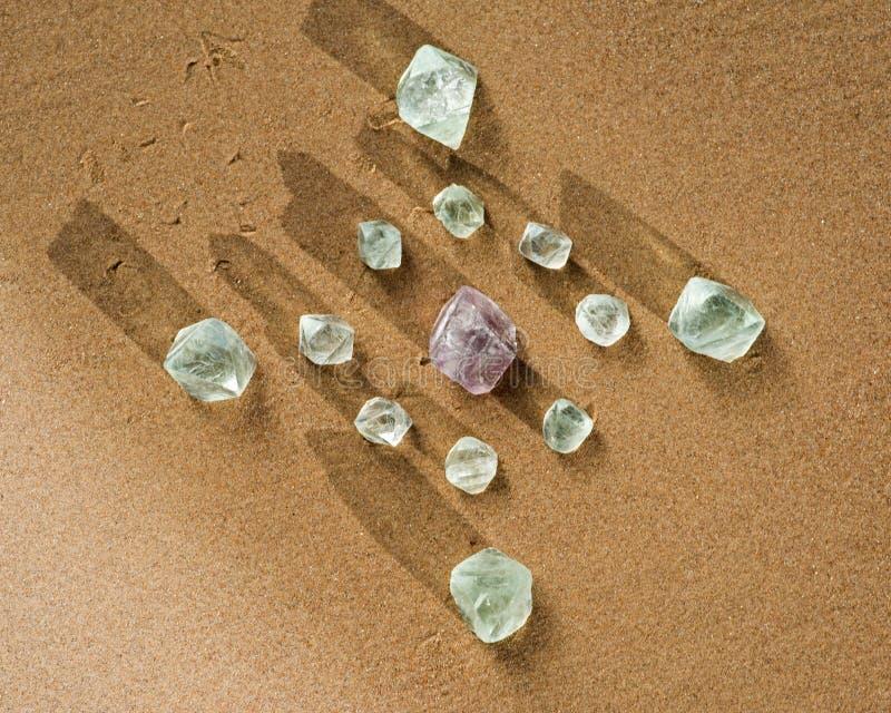 Кристаллическая решетка с кристаллами восьмигранника фиолетового и зеленого фторита естественными на пляже стоковые изображения rf