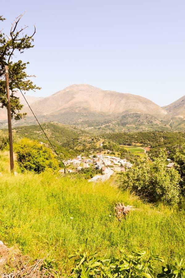 Критянин деревни садить на насест на холме среди стоковая фотография rf