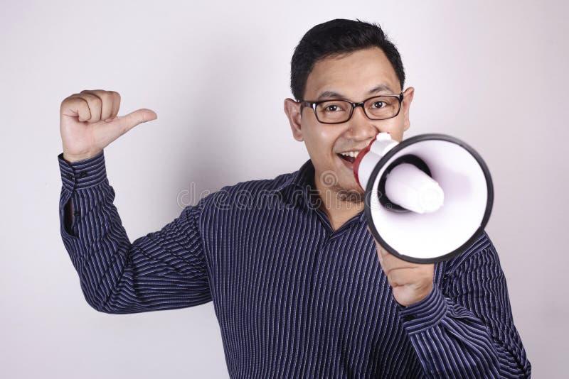 Кричать используя мегафон, выходя на рынок концепция молодого бизнесмена усмехаясь продвижения стоковое изображение rf