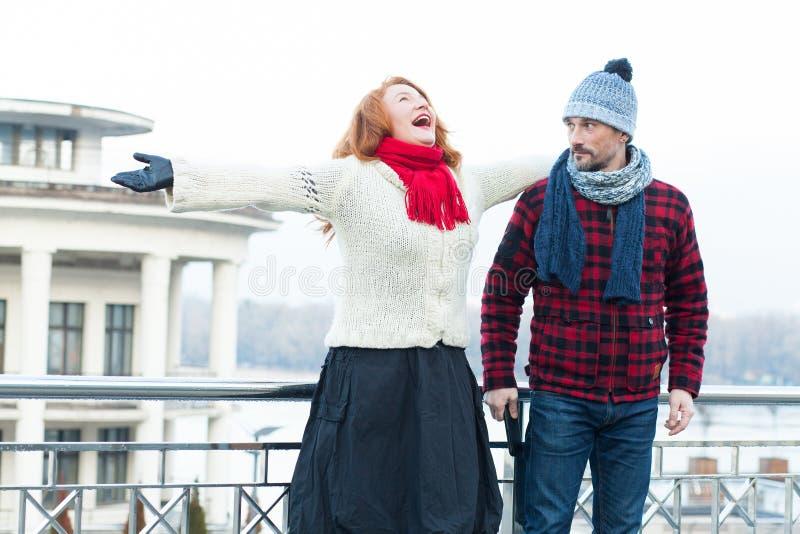 Кричащая красная женщина и парень волос смотря к ей Очень счастливая женщина плача на мосте и удивленном человеке стоковое изображение