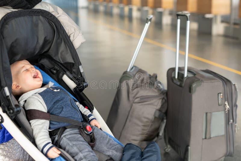 Кричащий ребенок сидя в прогулочной коляске около багажа на крупном аэропорте Ребенок в экипаже около счетчика стола регистрации  стоковые фотографии rf