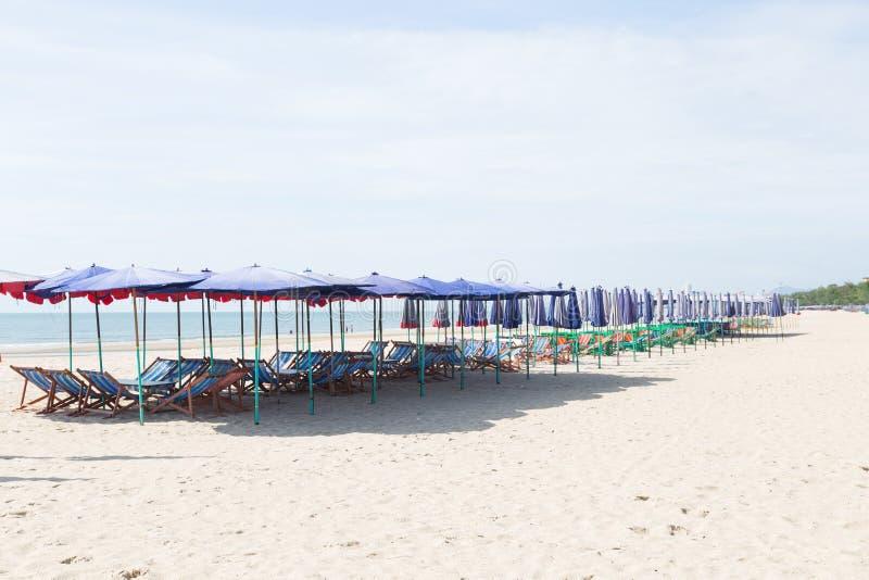 Кровати и зонтики на пляже стоковые изображения