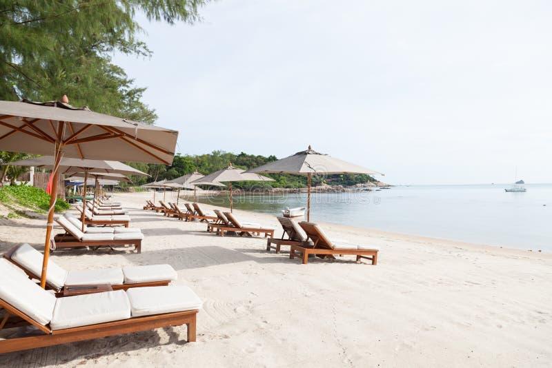 Кровати и зонтики на пляже стоковое изображение
