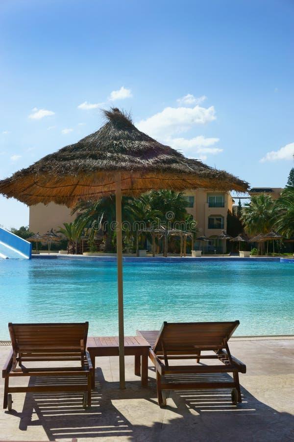 Кровати и зонтик Солнця вокруг бассейна стоковое фото