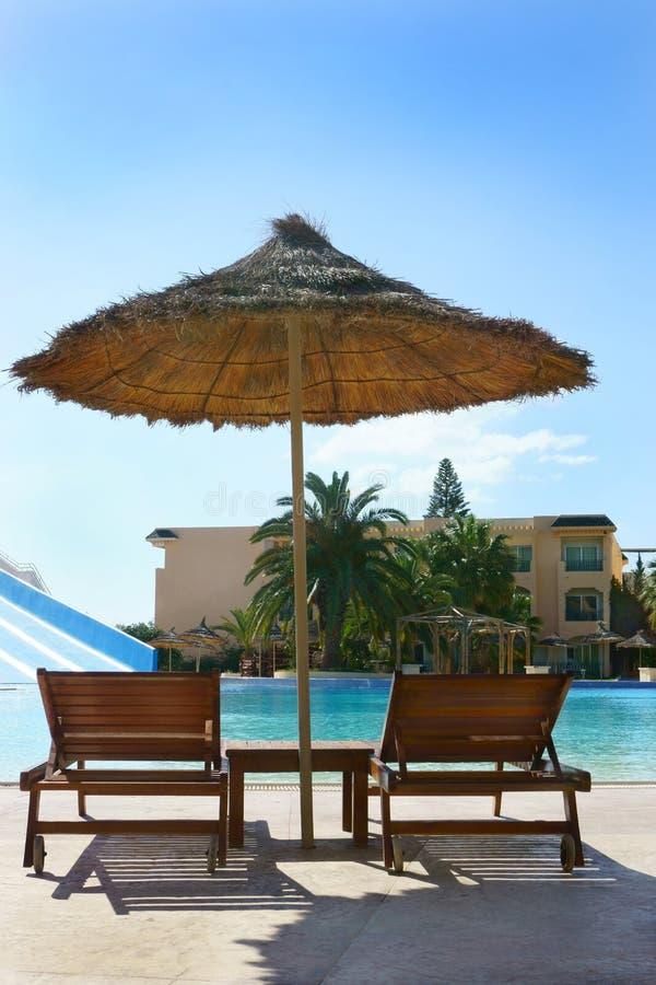 Кровати и зонтик Солнця вокруг бассейна стоковые изображения rf